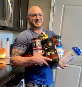 The best supplements for muscle growth - me holding supplements