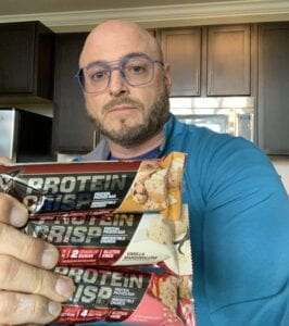NO Xplode pre workout reviews - me holding rice crispy protein bars