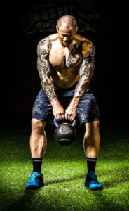 Crossfit and Pre Workout - man with tattoos swinging kettlebell
