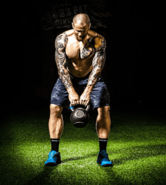 What Is The Best Pre Workout Energy Booster - man with tattoos swinging kettlebell