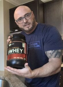 What Is The Best Low Calorie Protein Powder - woman with muscular stomach - ON gold standard whey protein review - container of gold standard