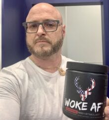 Bucked Up pre workout review - me holding a container of woke af pre workout