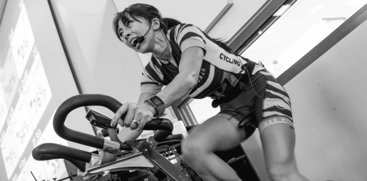 Stationary Bike Exercise Benefits - Woman doing spinning class