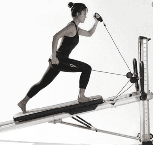 There are different resistance levels to keep your workouts challenging. - Woman using total gym fitness machine