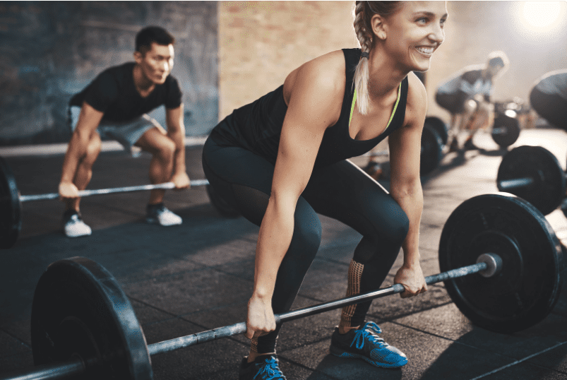 benefits of exercise and mental health - Lady lifting barbell while smiling