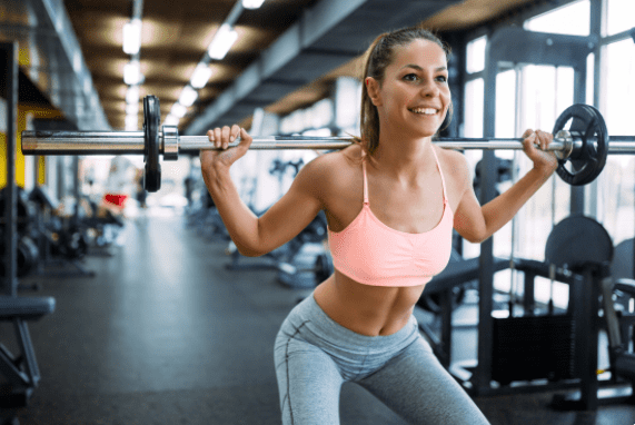what is a squat exercise - Woman doing squats while smiling