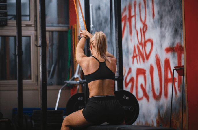 Best Exercise Bands Workout - woman doing resistance band exercises for the back at a gym